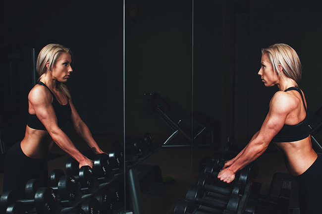 woman lifting weights and looking in mirror