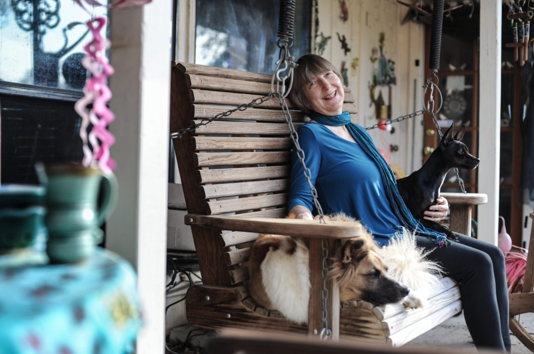 Carol on her front porch with rescue dogs, Holly and Inky. USA, 2015.