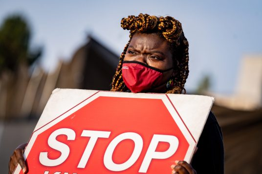 Gwenna Hunter stands outside a meat packing plant in silent protest during a cow vigil. Photo by Nikki Ritcher / #unboundproject / We Animals Media.