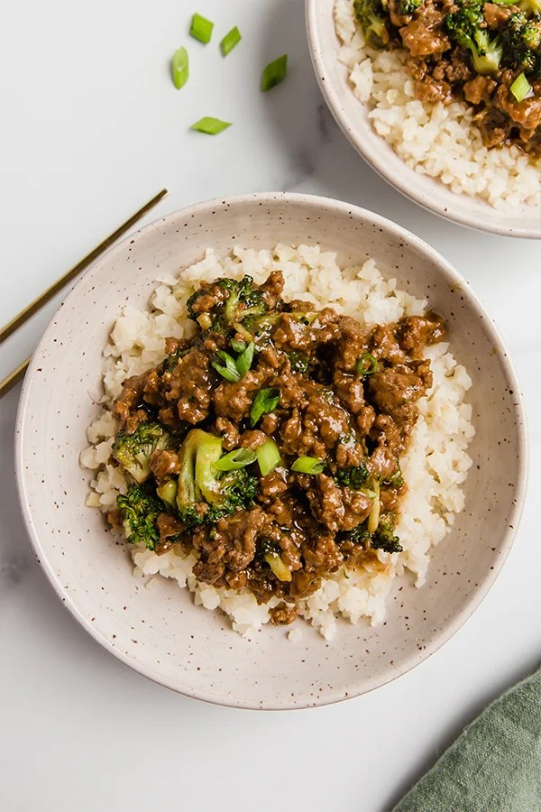 Ground beef and broccoli in two bowls with chopsticks