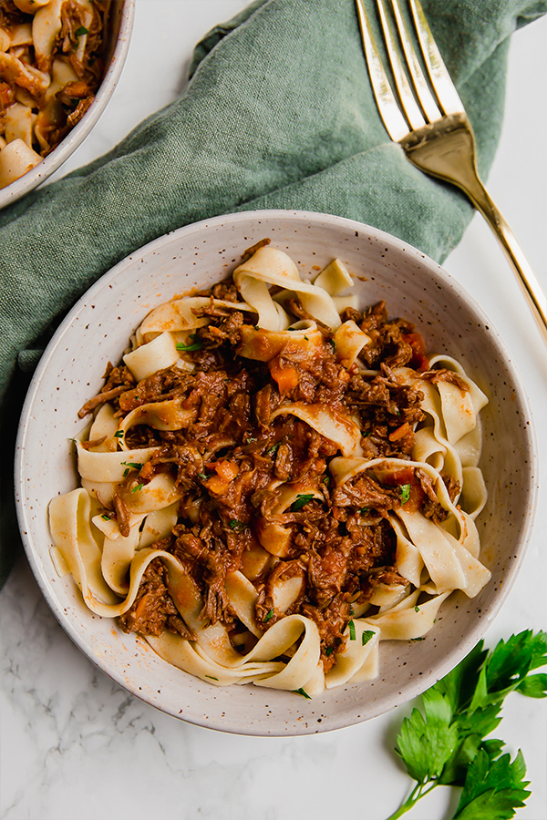 beef ragu in two bowls with green cloth and gold fork