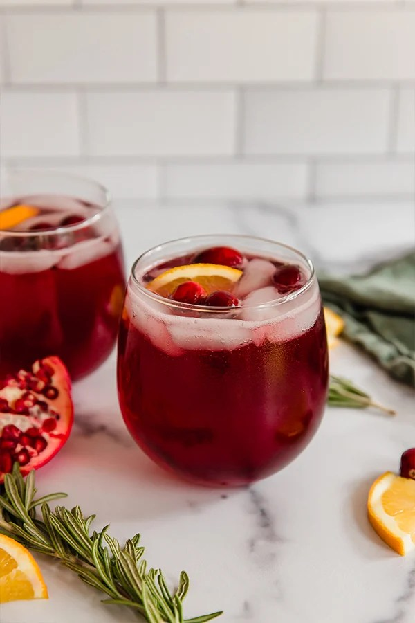 cranberry pomegranate holiday mocktail in wine glass