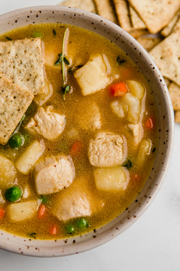 chicken pot pie soup in bowl with crackers