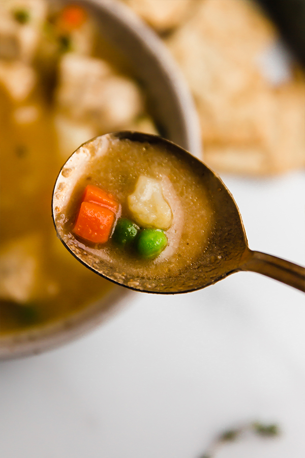 chicken pot pie soup in bowl with soup in spoon
