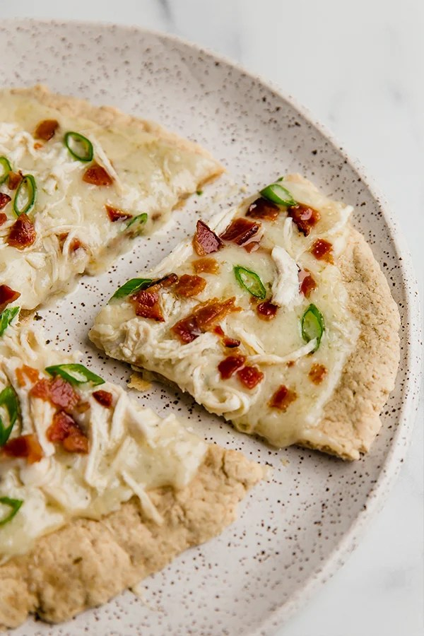 bacon ranch pizza on plate with slice