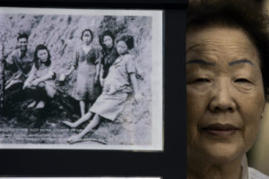 Former comfort woman Yong?Soo Lee's one wish is that the government of Japan officially apologize to women who were conscripted as sex slaves during World War II. With the proposed House Resolution 121 ? calling on the Japan to officially apologize for its crimes against as many as 200,000 women who were forced to serve Japanese soldiers ? before Congress, the 80?year?old South Korean woman was in Los Angeles on 7/14/07 to drum up support for the measure. On Saturday (July 14) she gave her testimony before a gathering of Christian pastors and leaders at Wilshire Presbyterian Church. She is photographed next to pictures of comfort girls that were on display at the church. (Photo by Gary Friedman/Los Angeles Times via Getty Images)