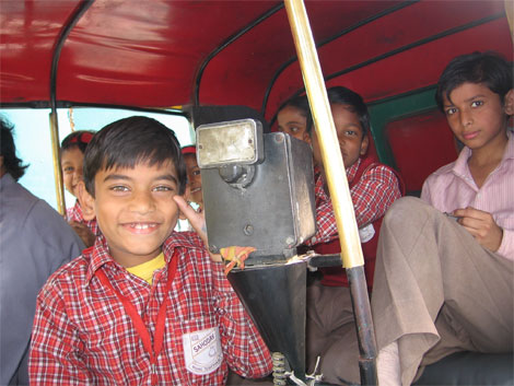 Boys crammed into one auto rickshaw.