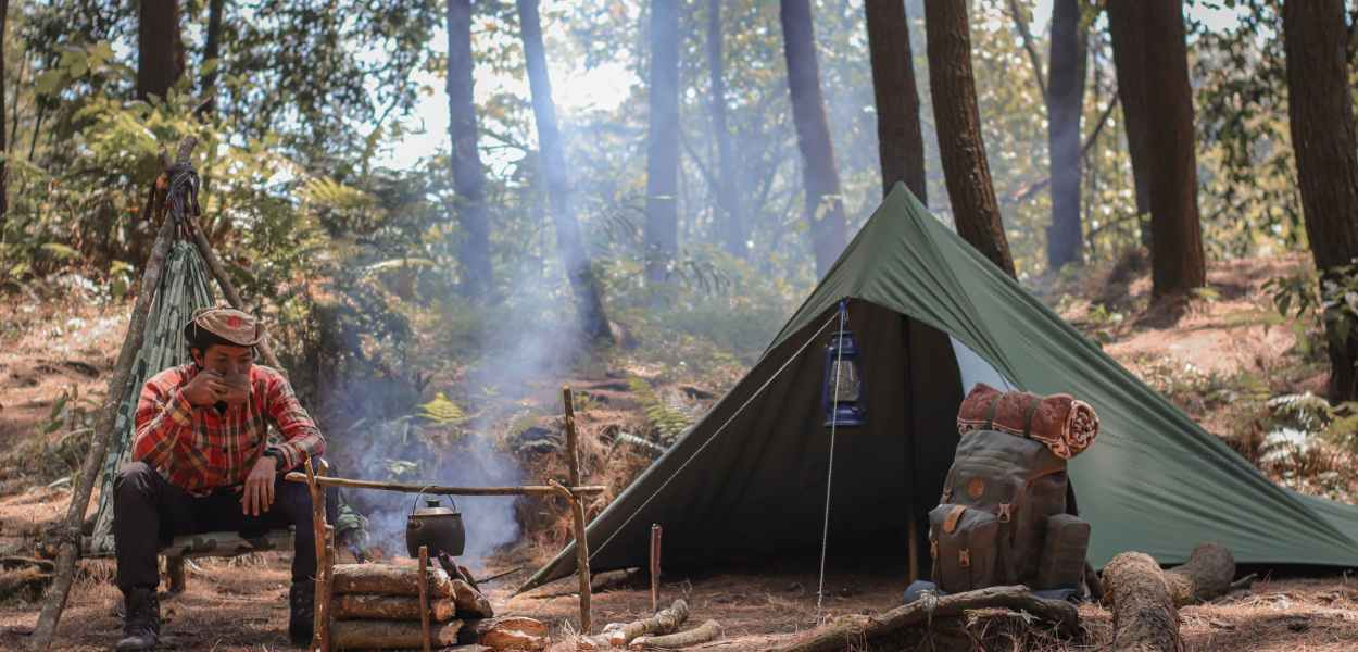 hiker resting near fire and tent during travelling