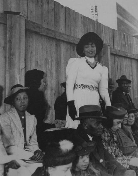 Zora Neale Hurston (standing) at a North Carolina College football game, 1939 in the North Carolina Central University Faculty and Staff Photograph Records, 1910-2005, University Archives, Records and History Center in the James E. Shepard Memorial Library, North Carolina Central University.