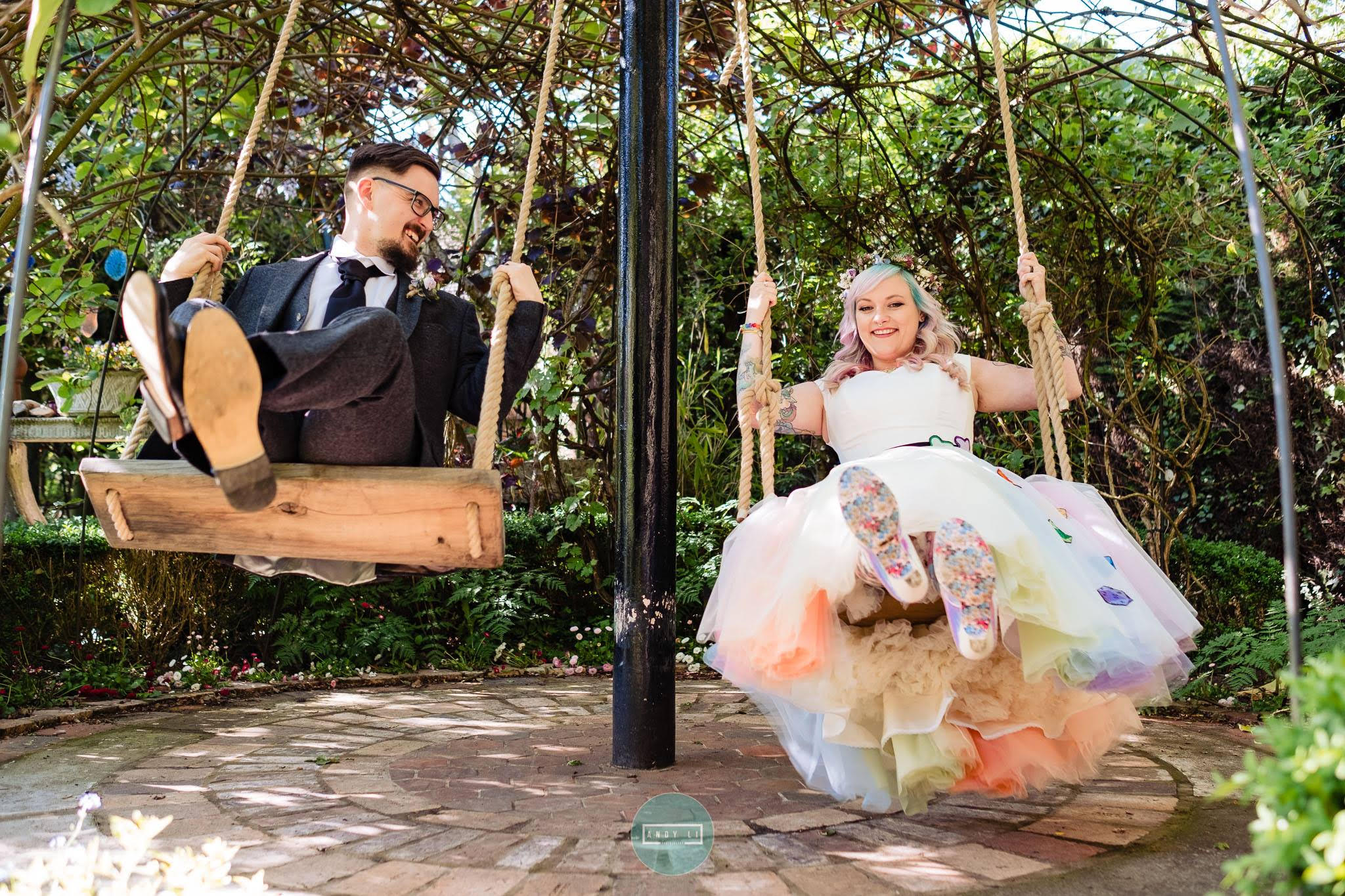 rainbow wedding themed wedding dress by the little wedding shop - colourful wedding inspiration - couple on swings - rainbow tulle layers - bespoke wedding dress inspiration with dice and irregular choice shoes