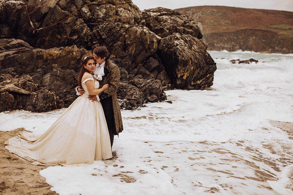 Labyrinth wedding - couple stood by the sea with the waves crashing in - cornwall wedding