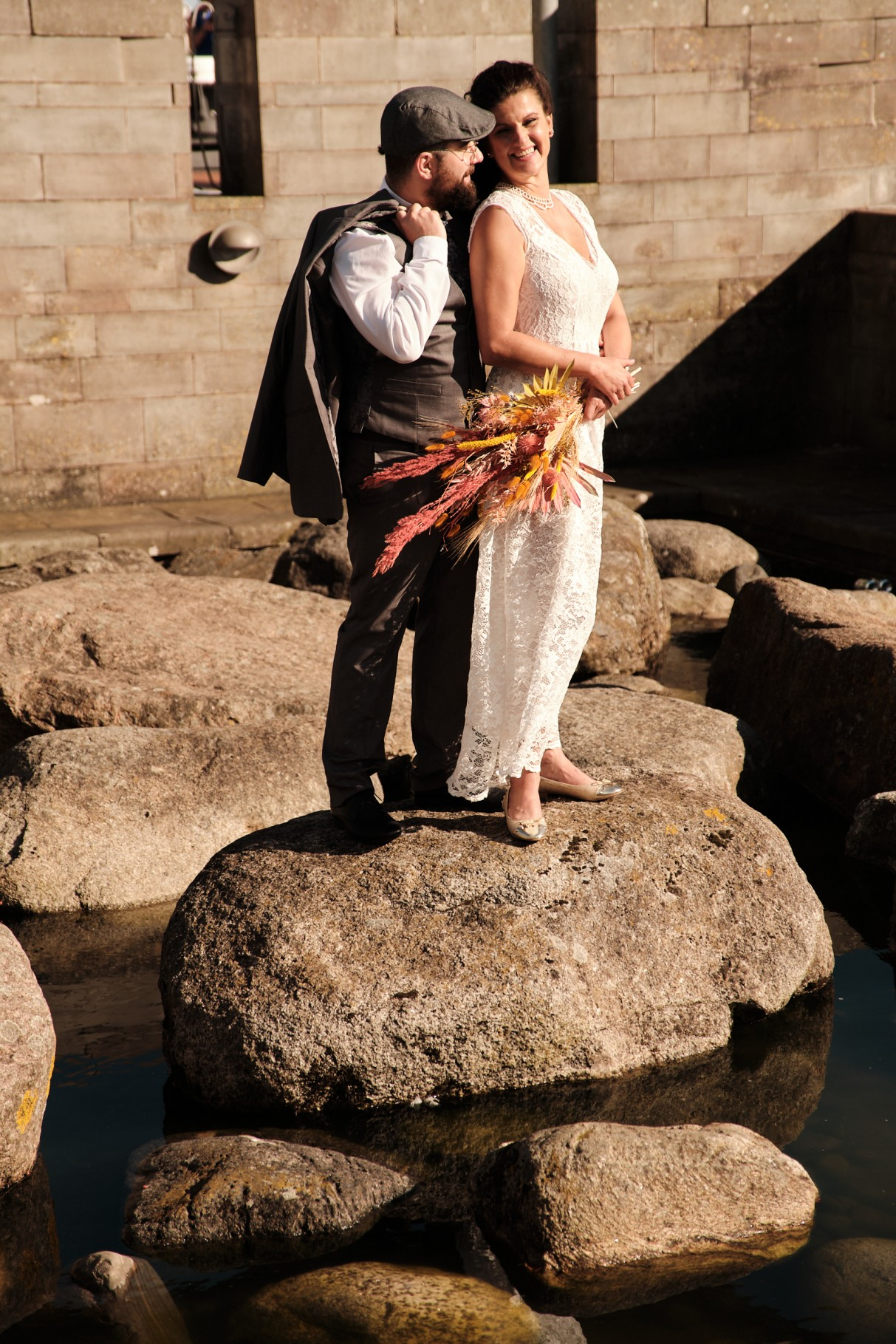city elopement- cardiff bay wedding- wales elopement- urban elopement - cardiff wedding - colourful summer wedding- couple standing on rocks