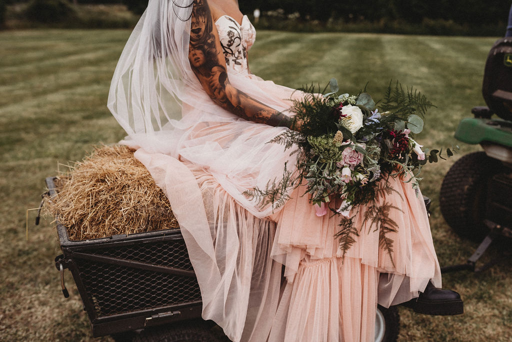 bride sitting on hay-bale - alternative farm wedding, edgy wedding, tattooed wedding, alternative wedding