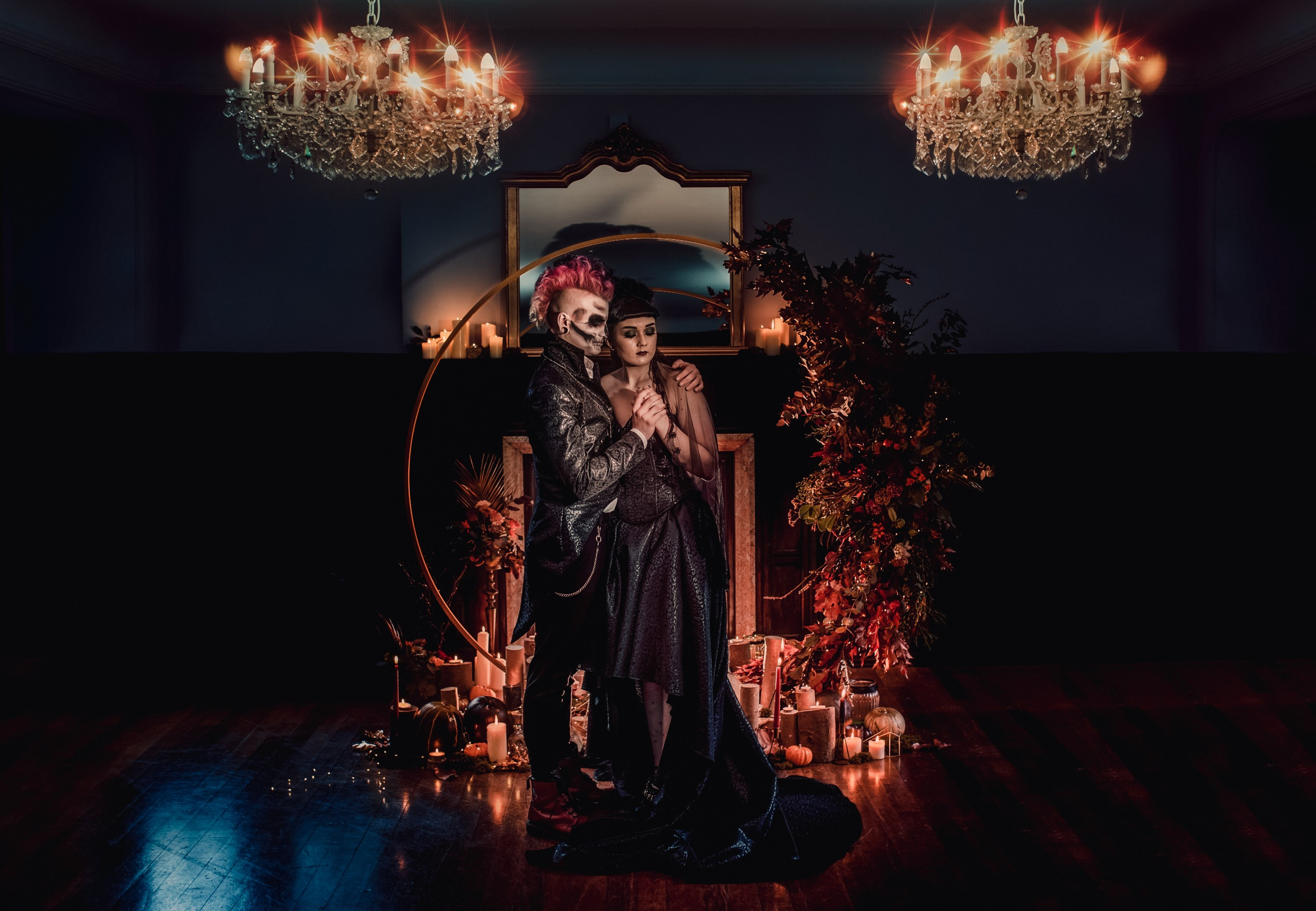 Gothic halloween wedding couple in the candlelight lit by two dramatic chandeliers against a dramatic floral arch backdrop at abbot oak wedding venue