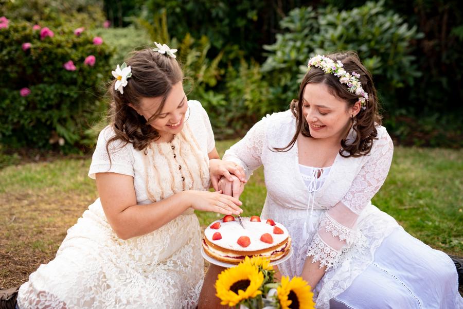 brides cutting cake in garden - garden micro-wedding - cottagecore wedding - simple elopement - romantic garden wedding - small wedding inspiration