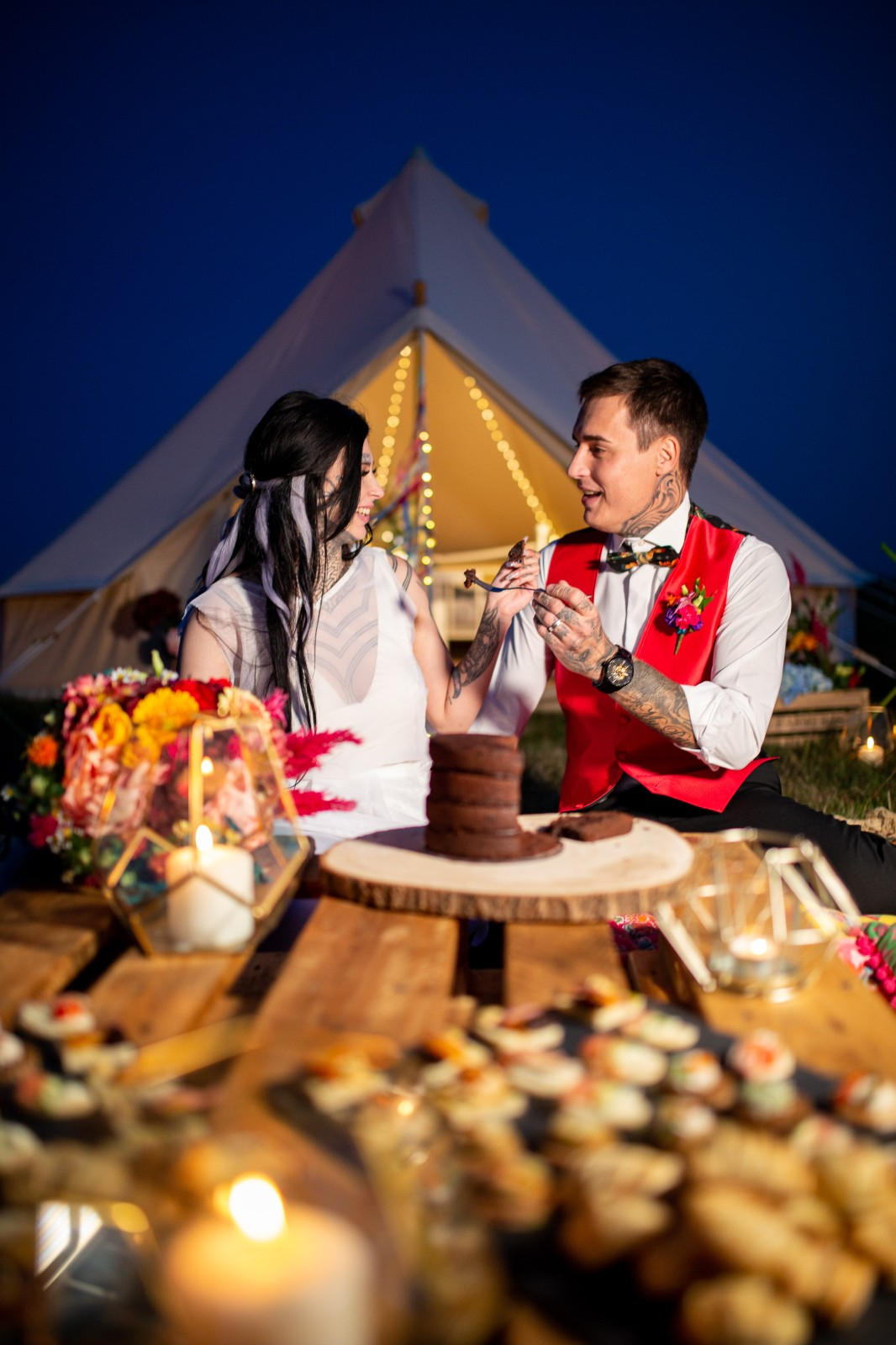 rainbow festival wedding - colourful wedding - quirky wedding ideas - tipi wedding - bride and groom eating cake