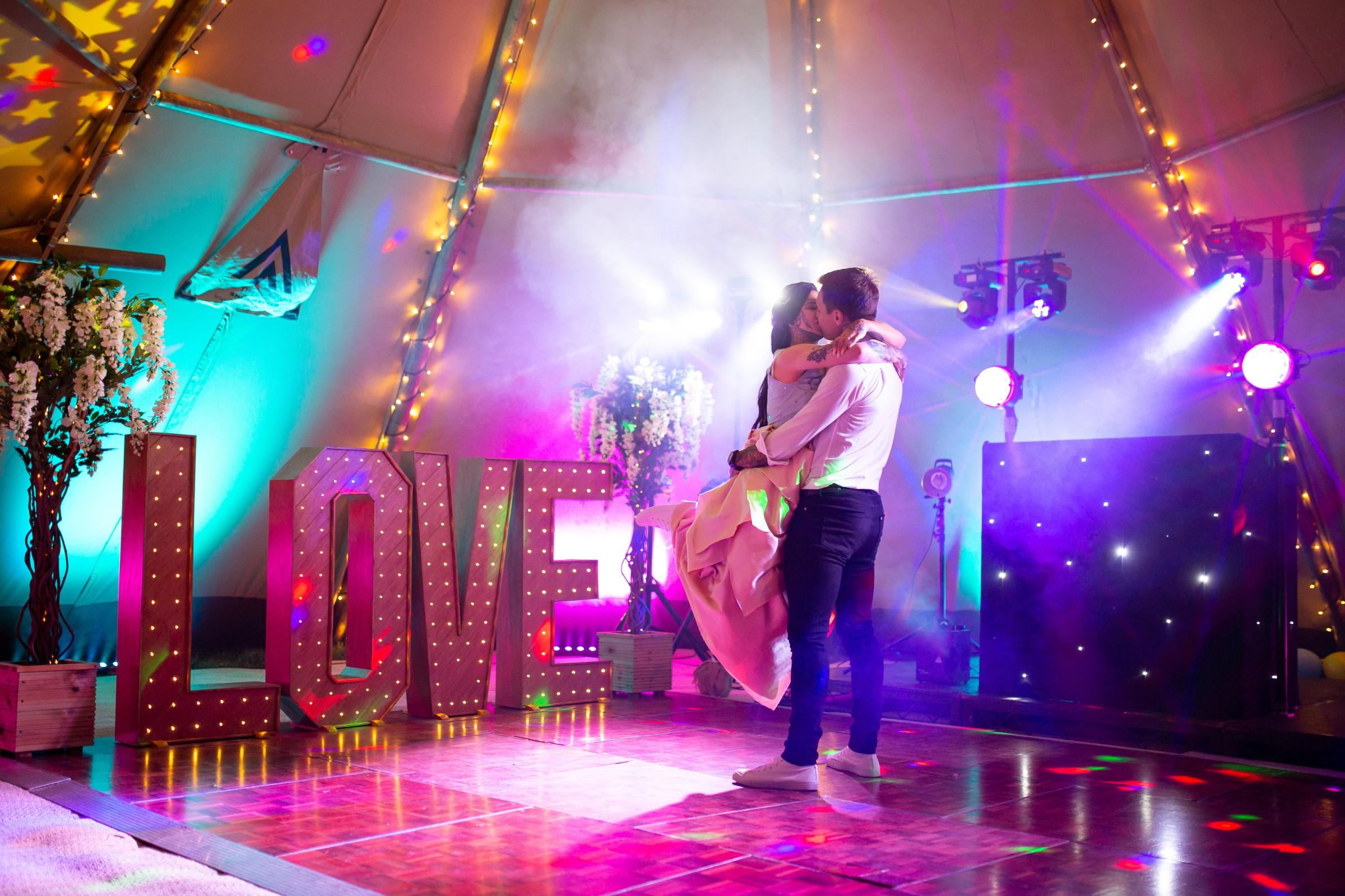 rainbow festival wedding - colourful wedding - quirky wedding ideas - neon love sign - bride and groom kiss on the dancefloor