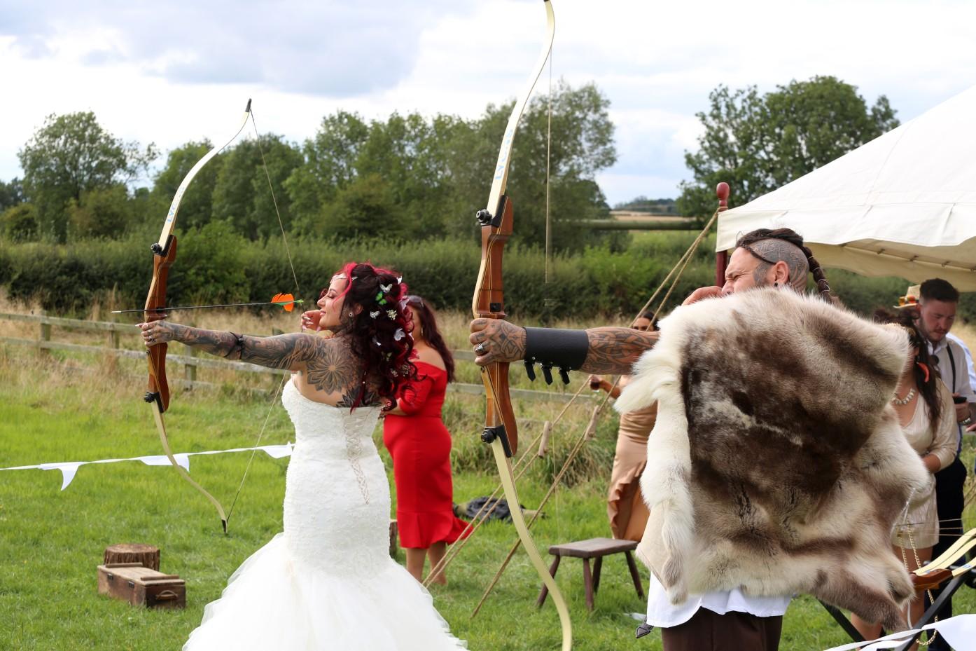 bride and groom doing archery - wedding archery - festival viking wedding - alternative wedding inspiration - unconventional wedding - alternative wedding blog