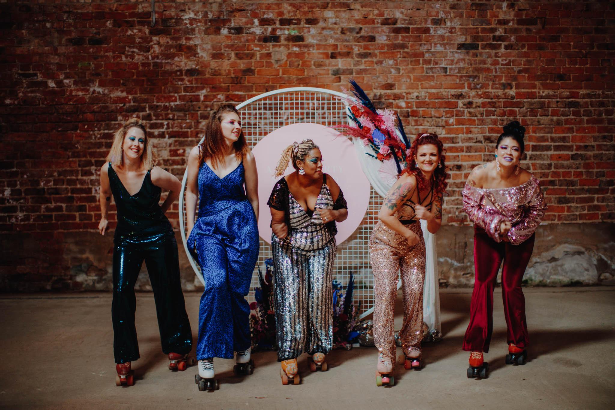 roller disco wedding - bridesmaids on roller skates - bridesmaid jumpsuits - unique bridesmaid ideas