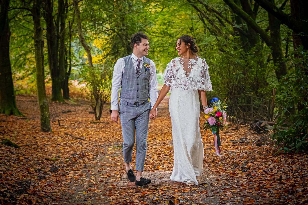 bride and groom walking in woodlands - boho wedding - outdoor wedding - unique wedding venue sussex - patricks barn