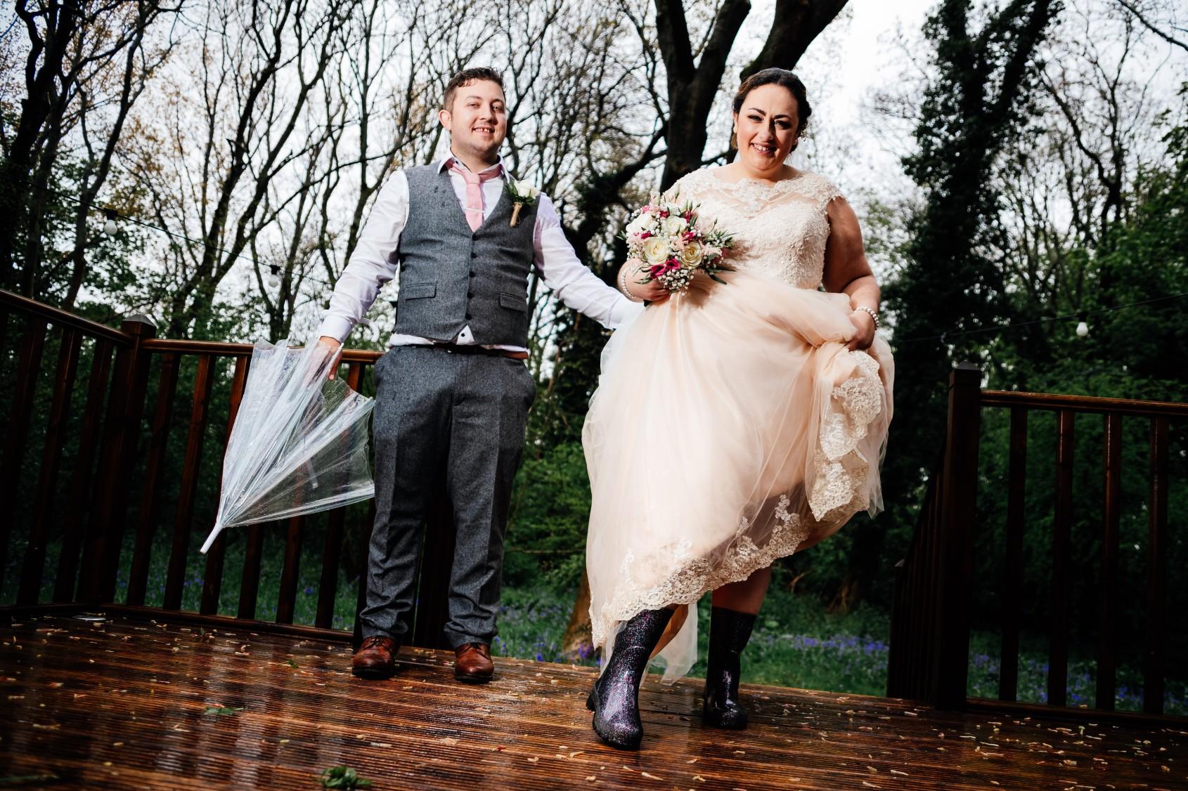 bride and groom dancing in the rain - fun wedding photos - rainy wedding - rain wedding advice - fun wedding planning - wedding planning blog - rain wedding photos