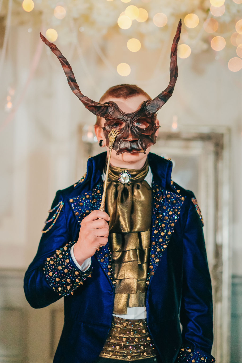 Groom holding masquerade mask for movie themed wedding day wearing royal blue suit with jeweled details