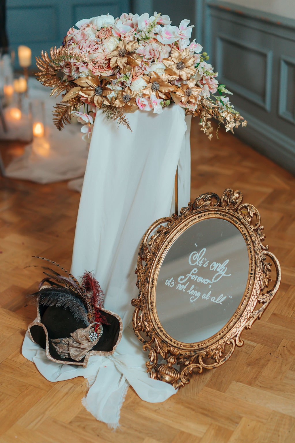 Mirror with the phrase ' its only forever, its not long at all' with flower arrangement on pedestal and groom's hat for a labyrinth themed wedding day