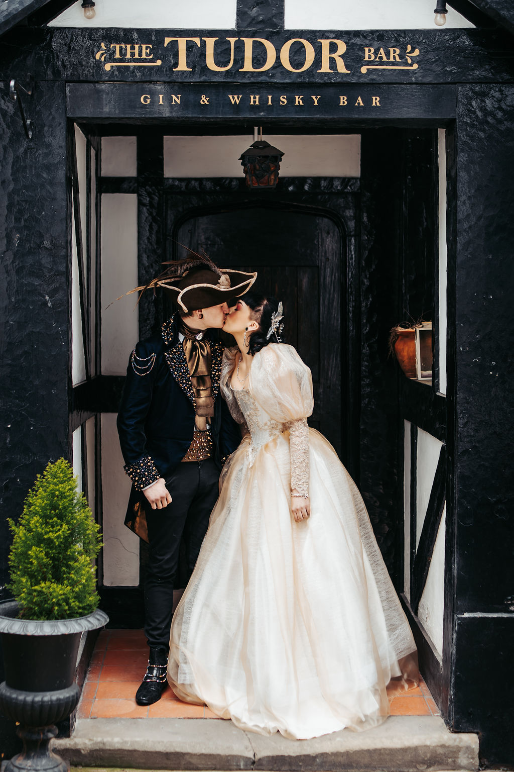 couple kissing in the door of the tudor bar, old bell hotel derby for a labyrinth themed wedding day