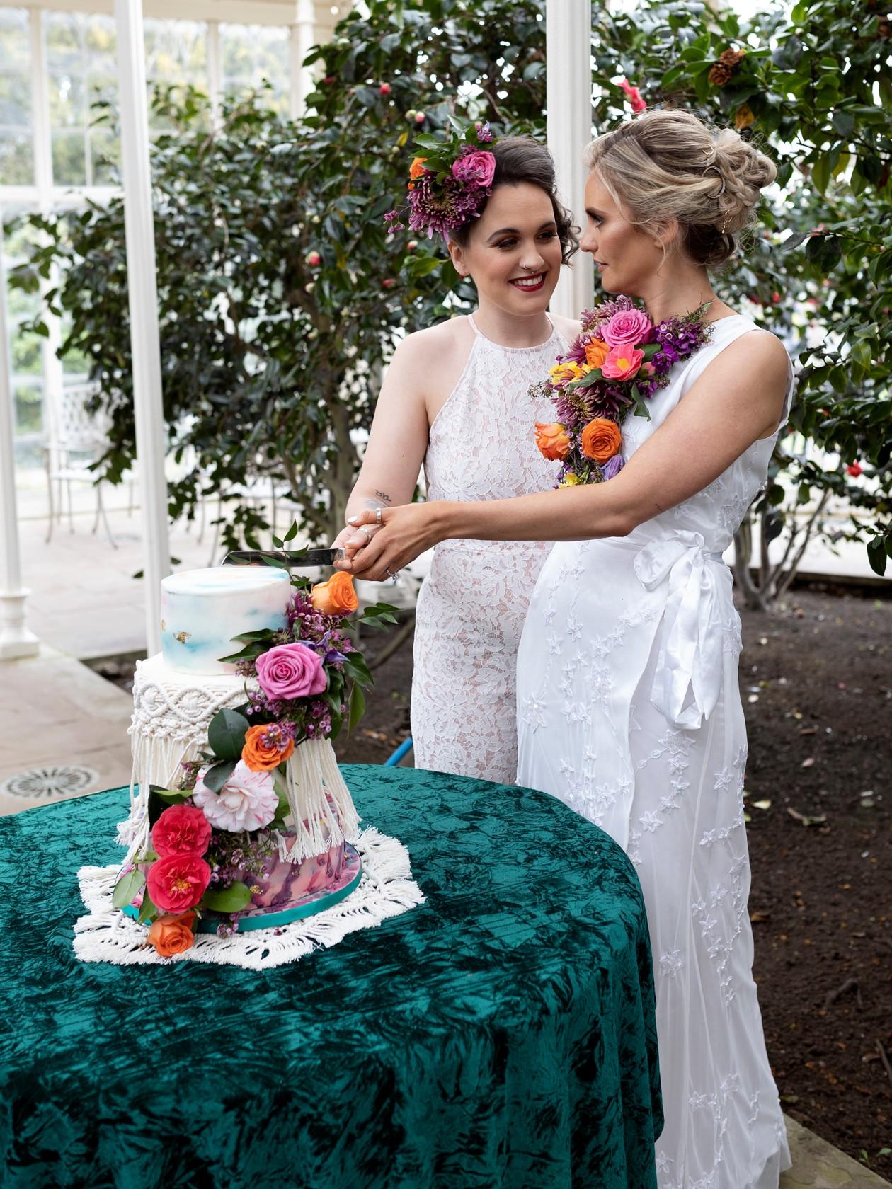 brides cutting cake, modern boho wedding, boho wedding cake - unique wedding cake - colourful wedding flowers