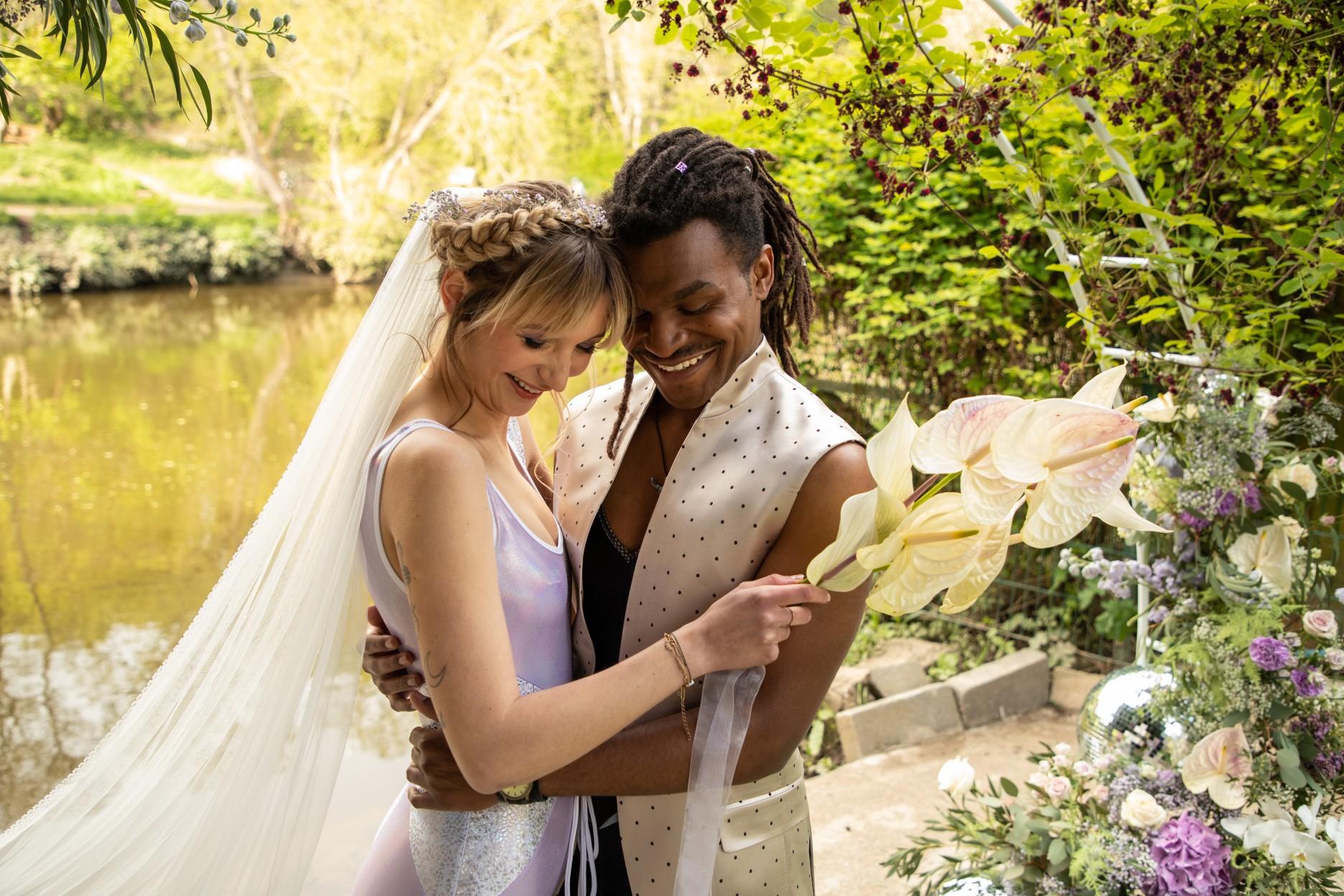 bride and groom smiling at wedding ceremony -modern festival wedding - unique wedding wear - wedding jumpsuit - wedding catsuit - festival bride - unique wedding wear