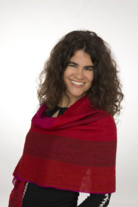 Pictured: Stephanie Elizondo Griest author photo; person wearing black clothing covering the top of the body, with a red shawl; the person has shoulder-length wavy dark-brown hair, light eyes, and is smiling.