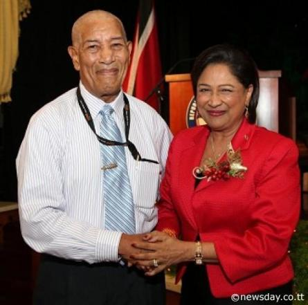 MEDIA GREETINGS: Prime Minister Kamla Persad-Bissessar, right, greets veteran journalist John Babb, Snr Associate Editor at yesterday's annual Media Christmas luncheon at the Diplomatic Centre, St Ann's. Babb,a journalist for 67 years moved a vote of thanks on behalf of media practitioners present  Author: Azlan Mohammed