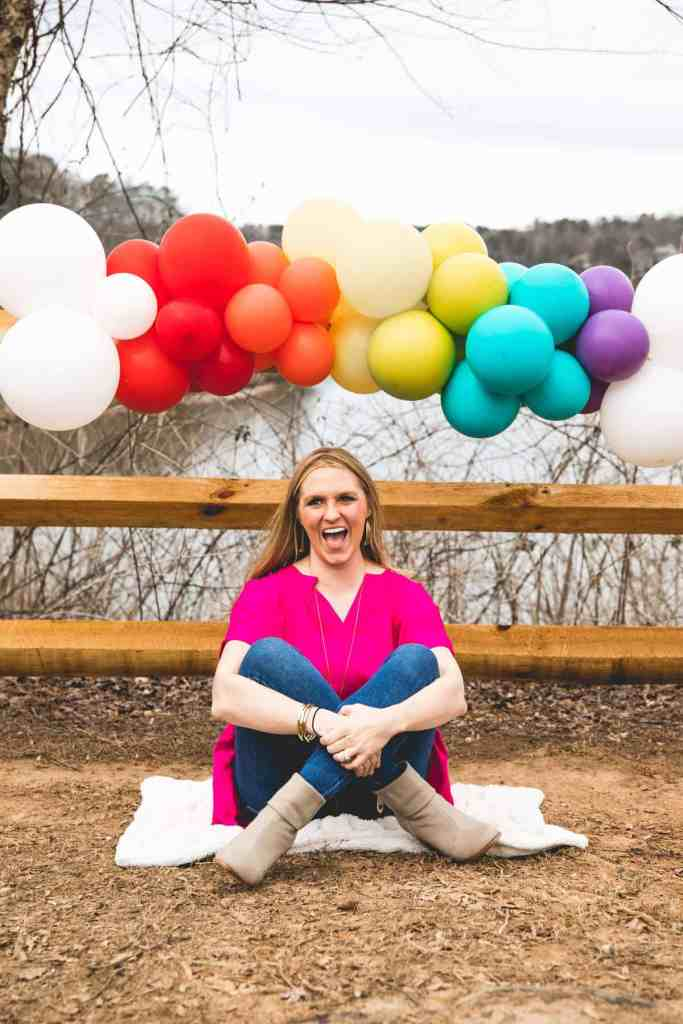 blonde-woman-in-pink=shirt-has-arms-wrapped-around-legs-as-she-laughs-while-sitting-under-a-rainbow-made-of-balloons-that-represent-her-rainbow-babies