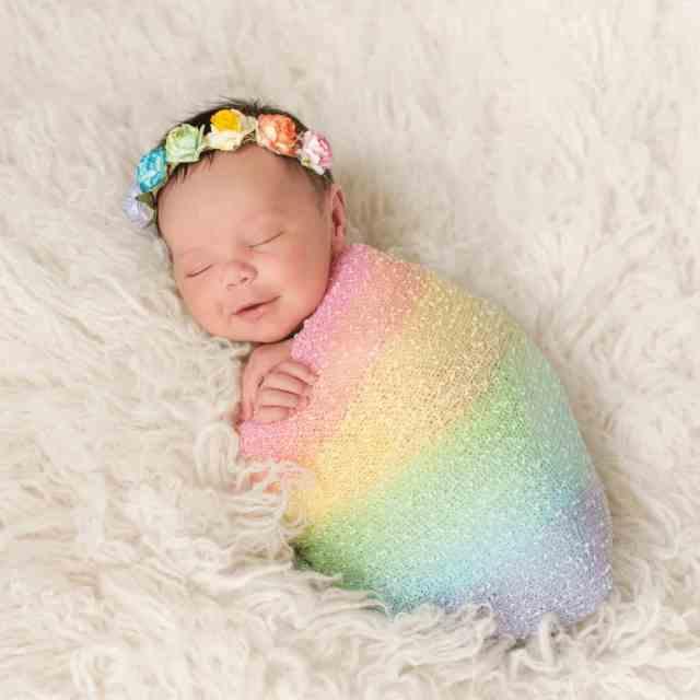 newborn-baby-with-dark-hair-and-rainbow-colored-flower-headband-lying-on-fuzzy-blanket-swaddled-in-rainbow-blanket