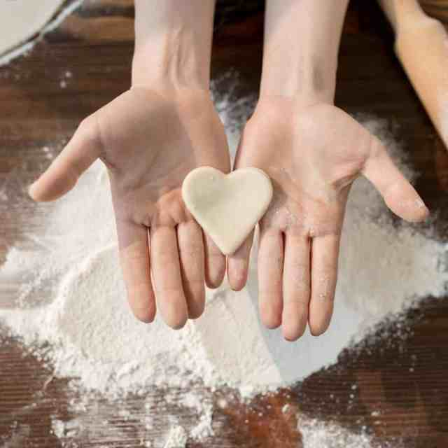 Hands holding up a heart-shaped piece of sugar cookie dough with flour in the background