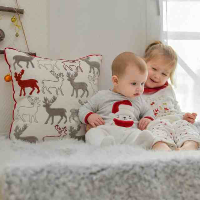 two babies wearing red and grey pajamas with a decorative pillow behind them displaying deer