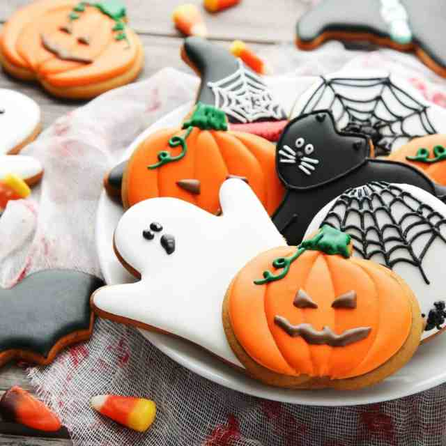halloween cookies like ghosts, pumpkins, spiders, and black cats on a plate on a decorated table