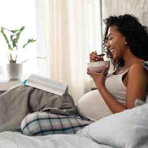 Pregnant woman reading and wearing maternity pajamas
