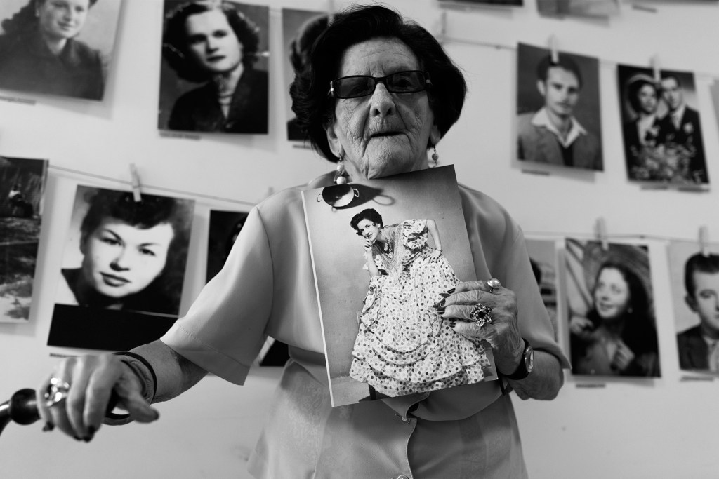 Black and white photo of an older woman holding a photo.. Behind her are headshots of other people.
