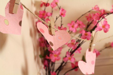 Adorable twine, clothes pin, and pink scrapbook paper heart tied up as a garland. Cherry blossom wired faux floral decor in the background. It makes the most adorable and simply pet rat shoot!