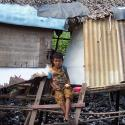 little boy sitting in front of a shack