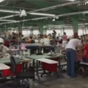 view of many people working in a clothing factory with machines all over