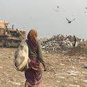 woman walks on trash mountain