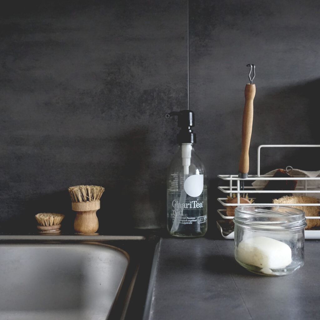 Minimalist kitchen tools for cleaning (sink, bristles, coconut oil soap)
