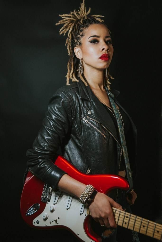 JUNO holding her red and white guitar in front of a black background.