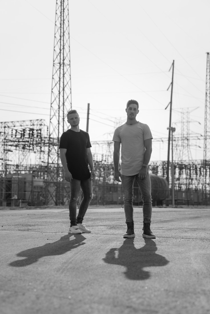 Country duo SixForty1, Austin Gee and Brooks Hoffman are pictured in front of a electric substation.