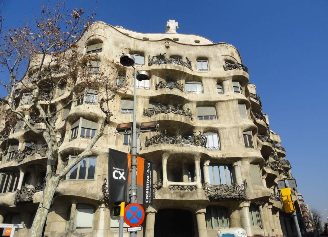 Golvende grijze gevel van Gaudi met balkons en grillige, smeedijzeren hekken