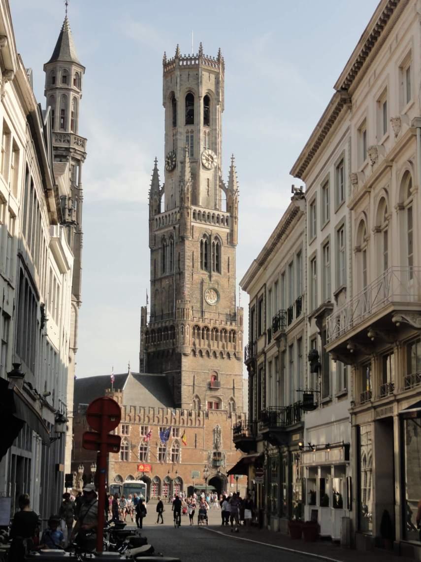 Belfort van Brugge gezien vanuit straatje met oude huizen