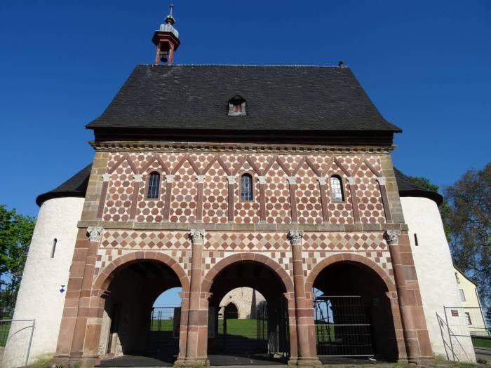 Poortgebouw van de abdij van Lorsch met roodwit geblokte voorgevel en drie poorten