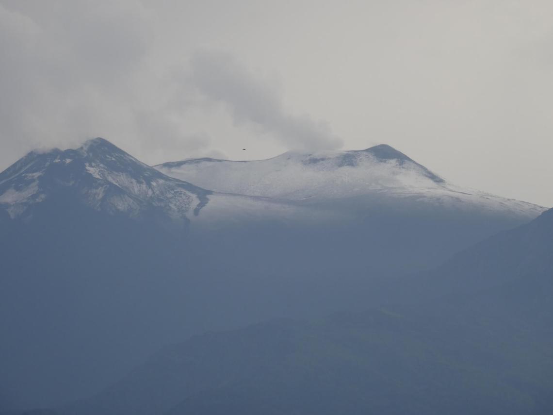 Rookpluimen verlaten een besneeuwde Etna